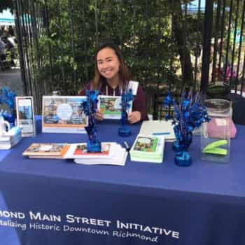 Summer intern Michelle Hong sitting at RMSI info booth, welcoming guests to Healthy Village Festival 2019